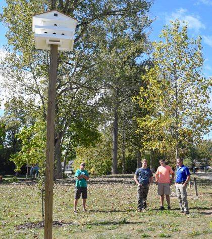 From left, local volunteer Dale Frymyer, Indian Lake sophomores Hunter Long and Rylee Halterman and Indian Lake State Park Manager George Sholtis discuss the purple martin birdhouse now located on Post Office Island at Indian Lake.