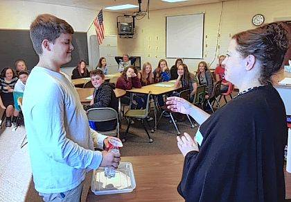 Kelli Bader coaches a Riverside student to pour a bottle of water into a cup without looking during the Choice program presented by the Midwest Regional Educational Service Center.