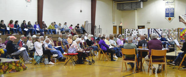 Bidders gather to purchase quilts during the auction.