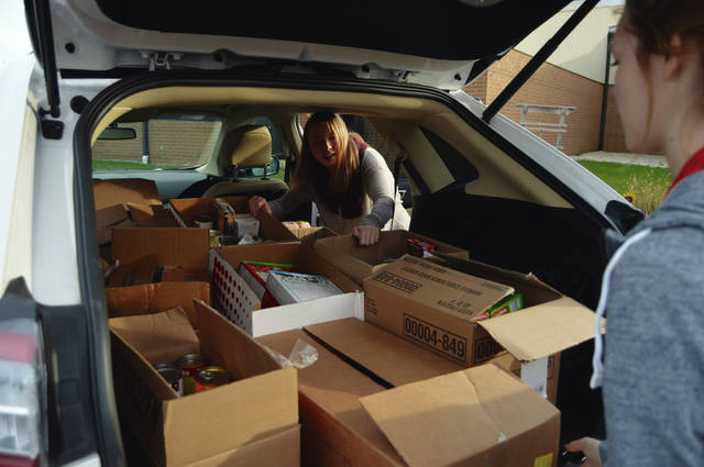 Indian Lake High School Student Council members Lindsay Berg, left, and Aubrey Grider, right, load boxes of donated food to take to the St. Vincent de Paul Food Pantry in Russells Point. Student councils from all three Indian Lake school buildings wrapped up the annual All District Food Drive just before Thanksgiving break. Students and staff stuffed 63 boxes with more than 2,400 pounds of nonperishable food this holiday season.