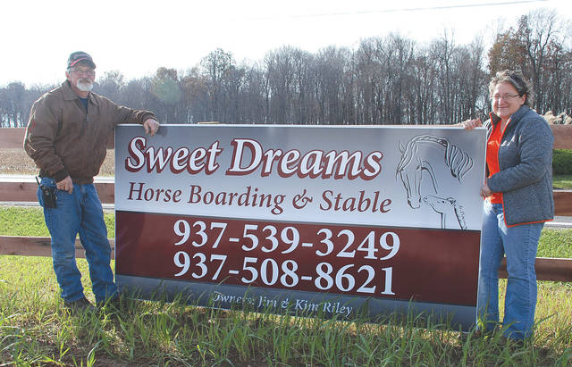 Jimmy Riley and Kim Barnes hold a sign for Sweet Dreams Horse Boarding and Stable on their property in the Bellefontaine area.