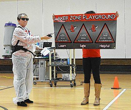 """Third grade teacher Pam Scarpella, wearing her """"Zone Buster"""" uniform, unveils a new banner to remind students of proper playground conduct. The skit accompanied a video for students to demonstrate the right way to play on the playground."""