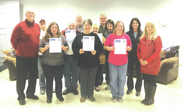 Steve Terrill, left, and Debbie Terrill, right, stand alongside a December 2017 class that completed the Mental Health First Aid course.