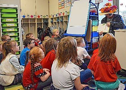 """Brenda Moots of Indian Lake Outfitters and The Depot in Lakeview wears a flowered hat as she reads her favorite children's book, """"Go Dogs, Go!"""" to Mrs. Downing's first grade class."""