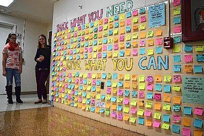 "Sophomore Danae Brown and math teacher Amber Shively stand by the ""Take What You Need, Give When You Can"" wall at Indian Lake High School."