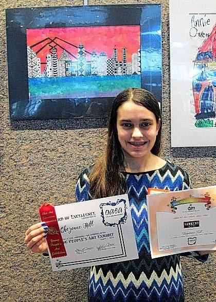 Indian Lake 8th grader Cheyenne Hill poses with her award beside her state-winning work of art, Color Theory Zentangle City.