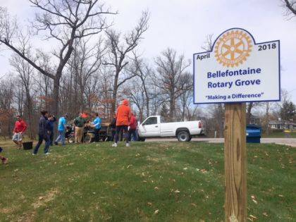 The Bellefontaine Rotary Grove sign is shown with a tree planting in the background.
