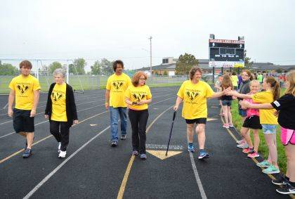 Jean Newmeyer slaps hands with students as she leads the Indian Lake Middle School Mini Relay for Life Survivors Lap on May 22. She was joined by her nephew Lee Newmeyer, her mother Kay Newmeyer, her brother Tim Newmeyer and her sister-in-law Debbi Newmeyer.