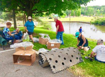Several gather to install floating wetlands at Indian Lake on June 8.