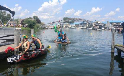"""At left, this year's winners, the father/daughter team of Doug and Jessica Burley, sail their homemade wacky boat, """"Fantasy Island."""" In the center, Brenda Ward of Norwalk and Eric Hall sail their boat, """"The Lost Island of Indian Lake."""" (center)"""