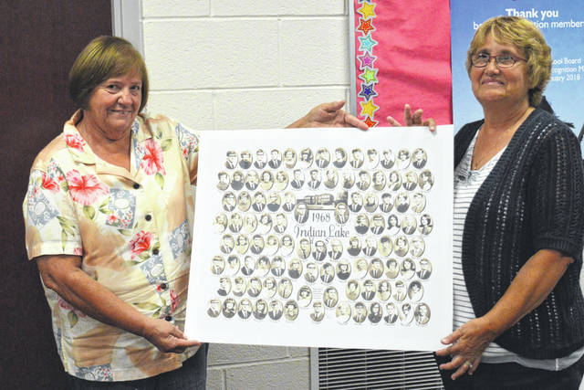 Mary Ann Parish and Diana Centers present the Indian Lake school board with the Class of 1968 composite to replace one that was lost.