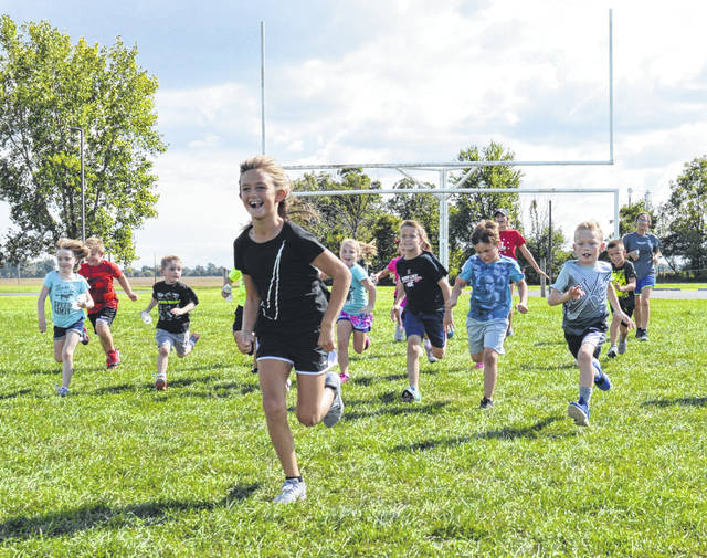 "Indian Lake second grader Mya Schroeder leads a pack of runners during a game of ""Stop & Go"" at the first season of Little Lakers Running Club."