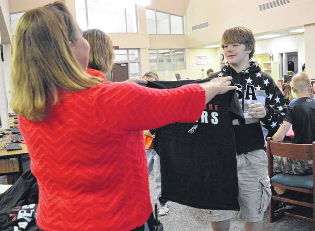 Indian Lake Middle School Co-Principal Missy Mefford presents a Laker T-shirt to new student Graysen Dowden during the ILMS New Student Breakfast.