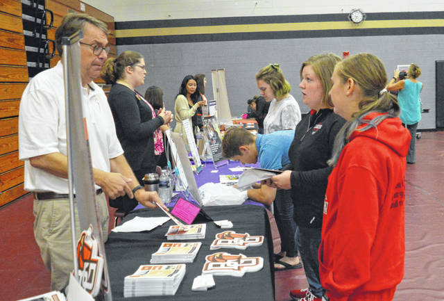 Indian Lake seniors Caitlyn Young, middle, and Nikita Scheifele speak with a representative of Bowling Green State University.