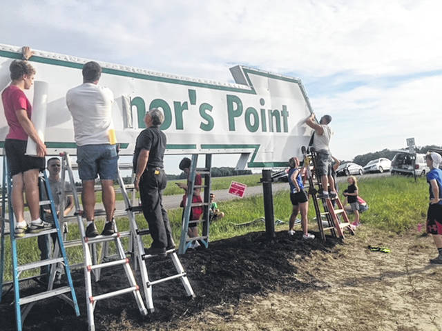 Ryan Braig, left, and several neighbors work on the O'Connor's Point sign as part of his Eagle Scout project earlier this summer.