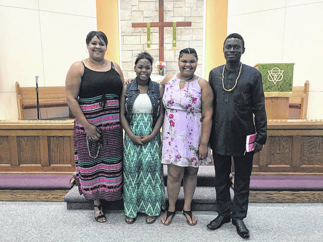 """Shown are Alex with Bellefontaine friends at DeGraff UMC. Alex traveled from Ghana to Columbus in 2017 and started working for a home health agency in Bellefontaine. This summer while on assignment, he met Deb Orr, Mary Rutan Community Health Nurse, at a DeGraff store. He told her he worked two jobs to send money to his Ghana village, where residents must walk 35 miles for medical aid. He said he was trying to raise funds for a vehicle for his village. Through Orr, he met her pastor, Pastor Mike of DeGraff UMC, who suggested avenues of assistance and helped arrange for Alex to send unsold items from the church's Aug. 4 """"Free"""" Sale to his village. The Church Missions Team agreed to help with postage to mail boxes to Ghana."""