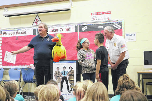 """Magic"" Tom Rozoff of Fire Fighter Phil and his friend, Lucky Duck, quiz fourth graders Audry Burton, Jaxon Snipes and Huntsville Fire Chief Tom Bodi."