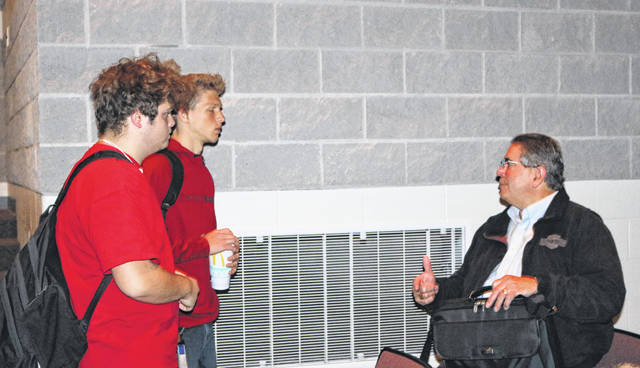 Indian Lake seniors Noah Reynolds and Devin Haver speak with Paul Benedetti after his presentation at the high school.