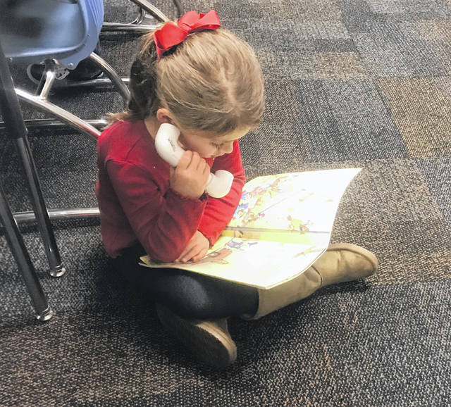 First grader Reese Imm uses a whisper phone to read.
