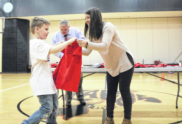Elementary Principal Molly Hall presents a Laker Zone shirt to first grader Kellen Wester.