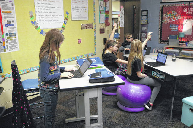 4th grader Lucy Buscher uses one of the stand up desks, while other students sit on balance balls in Christi Warneke's classroom.