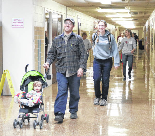 David and Lauren Glett push their daughter, one-year-old Natalie, in a stroller during the first night of Winter Walking at Indian Lake High School.
