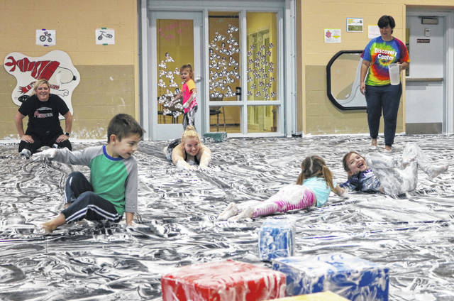 From left, Discovery Center students Calvin Smith, Crosley Stewart and Leonnah Line play in the Shaving Cream Ice Skating rink with volunteers.