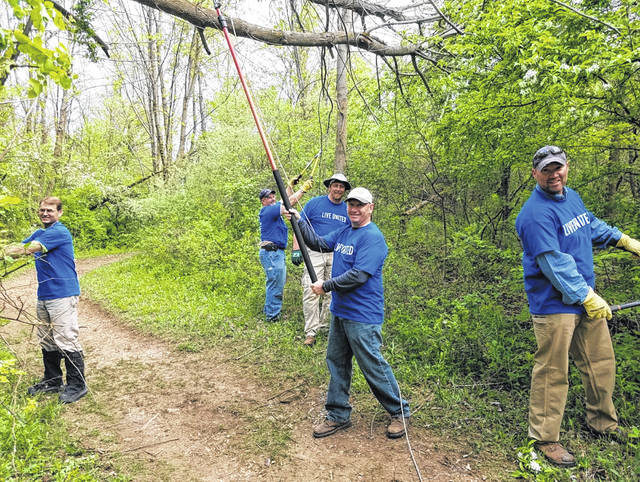Volunteers from Vectren clear brush and debris from walking paths at Indian Lake State Park during Community Care Day, 2018. United Way's signature volunteer event returns for a fourth year on Friday, May 10, and the organization is recruiting service projects from non-profits, parks and government agencies for completion by teams of corporate volunteers on that date.