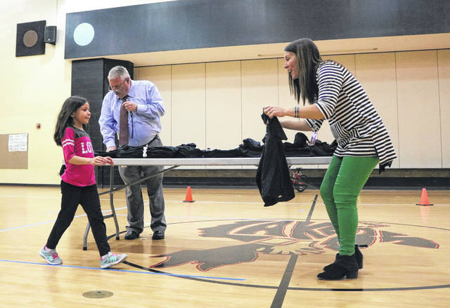 Indian Lake Elementary co-principal Molly hands a redesigned Laker Zone shirt to first grader Ally Stillgess.