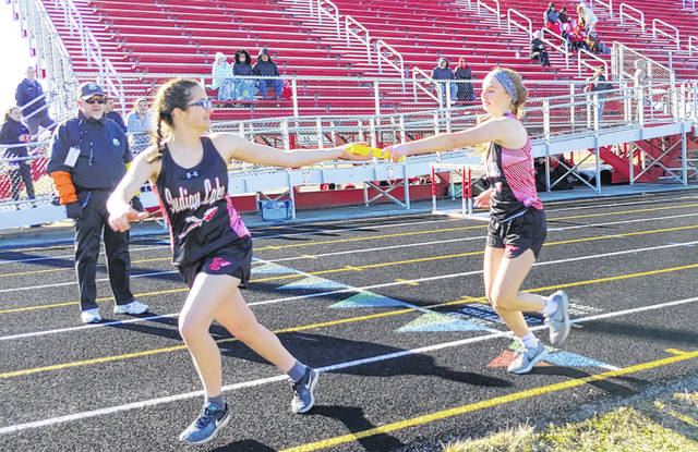 Ella Wagner passes the baton to Rachel Wahl in the 4x800 relay.