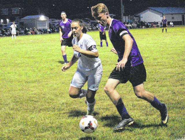 Gallia Academy's Trinity Eggers (4) battles Chesapeake's Cole Mills for possession of the ball during Thursday night's Ohio Valley Conference soccer match in Centenary, Ohio.