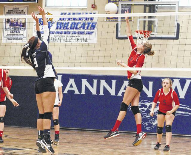 Point Pleasant junior Madison Hatfield, second from right, hits a spike attempt past a Hannan defender during Game 3 of Thursday night's volleyball match in Ashton, W.Va.