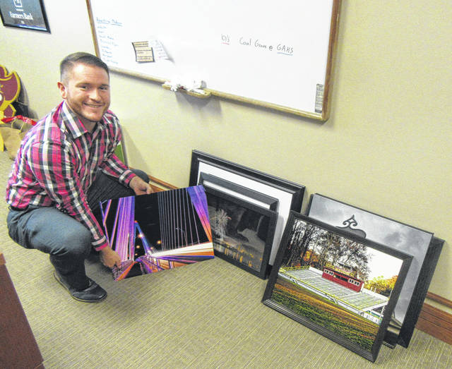 MLAA co-president Dru Reed is pictured with some of the photos donated for the silent auction.