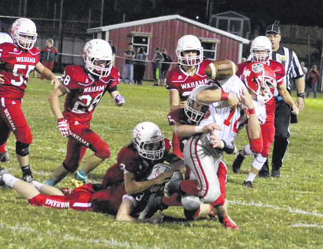 Members of the Wahama defense knock the ball loose from Trimble running back Connor Wright (10) during the second quarter of Friday night's Week 6 TVC Hocking football contest in Mason, W.Va.