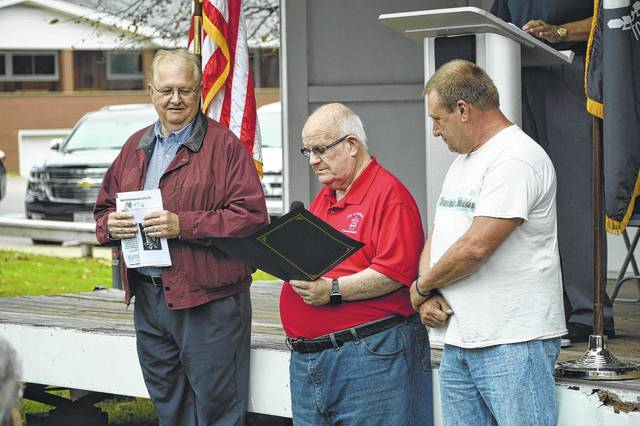 Gallia City Commission President Tony Gallagher, center, shares a proclamation from the city recognizing Sept. 15 as POW and MIA Recognition Day. City Commissioner Mike Fulks, right, and Gallia Commissioner Harold Montgomery, left, share in the measure.