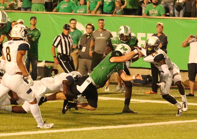 Marshall quarterback Chase Litton extends the ball over the goal line for a fourth quarter touchdown on Saturday night during a 21-0 victory over Kent State in a non-conference football contest at Joan C. Edwards Stadium in Huntington, W.Va. (Bryan Walters|OVP Sports)