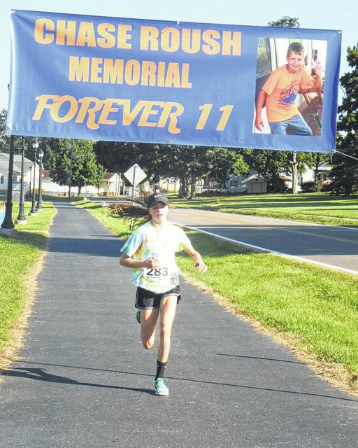 Sydney Roush is the first to cross the finish line during the Chase Roush Memorial 5K run on Saturday morning at Star Mill Park.