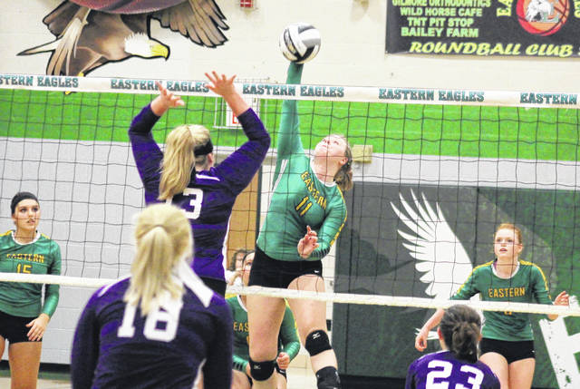 Eastern senior Mackenzie Brooks (11) spikes the ball over the net in front of teammates Morgan Baer (15) and Allison Barber (right), during the Lady Eagles' 3-0 win over Miller on Tuesday in Tuppers Plains, Ohio.