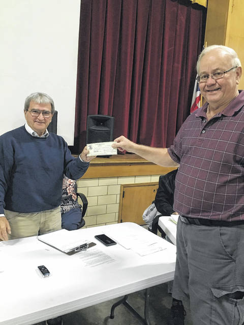 Kenny Utt, right, presents a check to Council President Emerson Heighton.