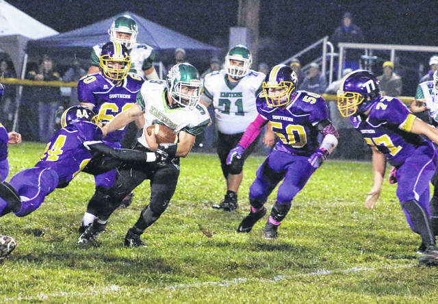 Eastern senior Josh Brewer (9) is swarmed by Southern defenders Gage Barrett (44), Sean Myers (60), Alex VanMeter (50) and Austin Arnold (77) during a first half carry Saturday night in a Week 10 TVC Hocking football contest at Roger Lee Adams Memorial Field in Racine, Ohio.