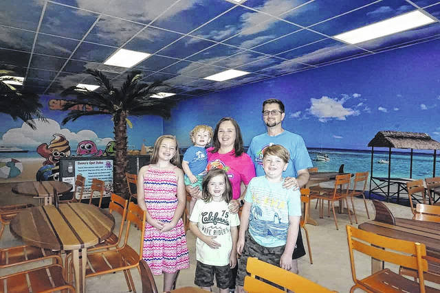 Beaches and Cream, located in the Walmart shopping plaza at Mason, was opened by the Grate family in August. The shop features 14 flavors of frozen yogurt, as well as other food treats, a playground area, and a room for birthday parties and other events. Pictured in front of the beach wall mural and cloud ceiling tiles are owners Tony and Miranda Grate, with their four children, Elliotte, Lane, Levi and Lachlan.