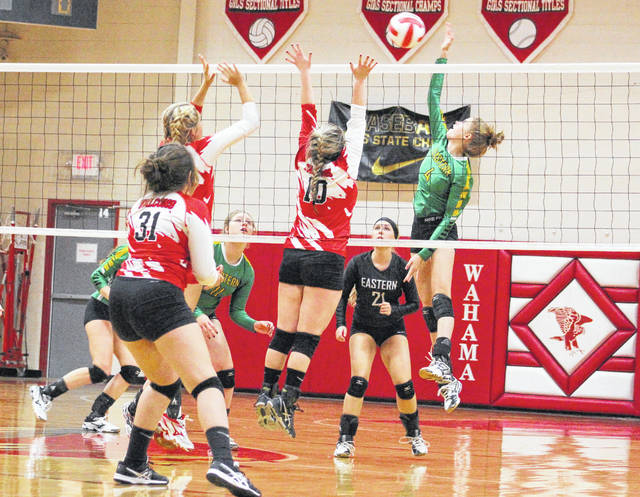 Eastern freshman Jenna Chadwell (4) hits a spike attempt over a pair of Wahama blockers during Game 2 of Tuesday night's TVC Hocking volleyball contest at Gary Clark Court in Mason, W.Va.