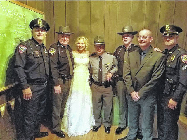 The men who danced with Mikaya (Poling) Wroten to honor the memory of her father. From left to right are past Gallipolis Police Chief Roger Brandeberry, Gallia Sheriff's Office Deputy James Pratt, Mikayla (Poling) Wroten, Ohio State Highway Patrol Trooper Marvin Pullins, Gallia Sheriff Matt Champlin, past Ohio Highway Patrol Trooper Robbie Jacks and Gallipolis Police Officer Adam Holcomb.