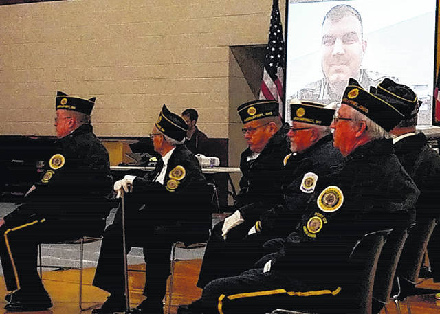 Captain Matt Ashcraft can be seen on the projector screen behind members of American Legion Feeney Bennett Post 128 during Friday's Veterans Day program at Meigs Middle School.