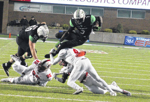 Marshall freshman Tyler King (3) attempts to hurdle over WKU junior Drell Green (9), in front of fellow MU freshman Will Ulmer (50), during the Herd's 30-23 victory on Saturday in Huntington, W.Va.