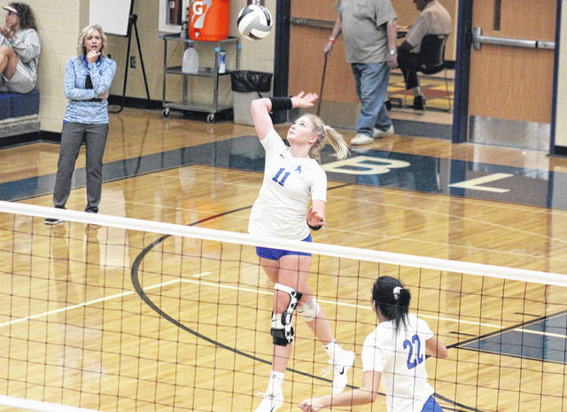 GAHS junior Ashton Webb (11) goes up for a spike in front of teammate Maddie Wright (22) and head coach Janice Rosier (left), during the Blue Angels' sweep of Fairland on Sept. 21 in Centenary, Ohio.