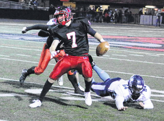 Point Pleasant junior quarterback Cason Payne (7) avoids a Philip Barbour defender while looking downfield for an open receiver during the first half of a Nov. 11 Class AA opening round playoff game at OVB Field in Point Pleasant, W.Va.