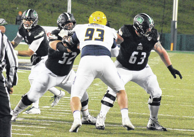 Ohio senior Jake Pruehs (52) and junior Joe Anderson (63) block for quarterback Nathan Rourke (left), during the Bobcats' 38-10 win over Toledo on Nov. 8 in Athens, Ohio.