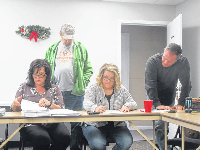 Deputy Director Tammy Cline and Director Angie Robson count the votes for Columbia Township Trustee as Board of Elections members Charlie Williams and Jimmy Stewart look on.