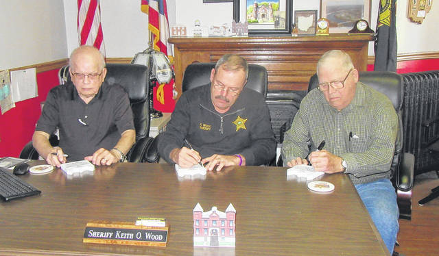Meigs County Sheriffs Robert Beegle, Keith Wood and Ralph Trussell sign the Meigs County Jail Cat's Meow buildings on Tuesday morning at the Sheriff's Office.